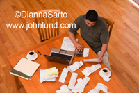 Picture of a man doing his tax preparation at home with his laptop and calculator. Piles of receipts bills and invoices scattered on the table.